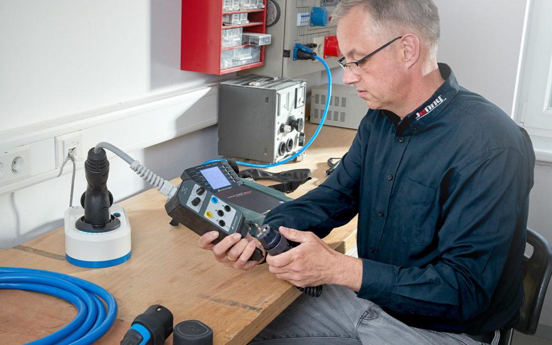 Energielösungen: eine Fachkraft für Elektrotechnik bedient ein technisches Gerät