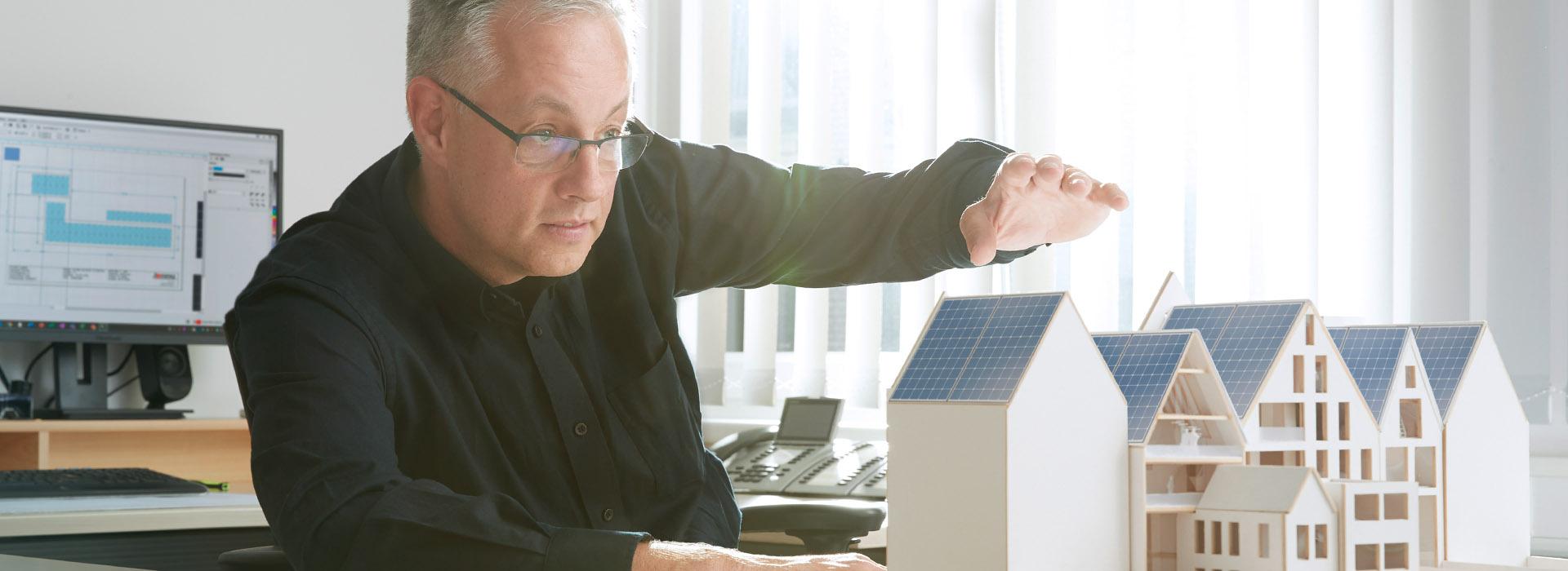 Energielösungen: Eine Fachkraft für Elektrotechnik veranschaulicht seine Vision anhand von einer Haus-Miniatur