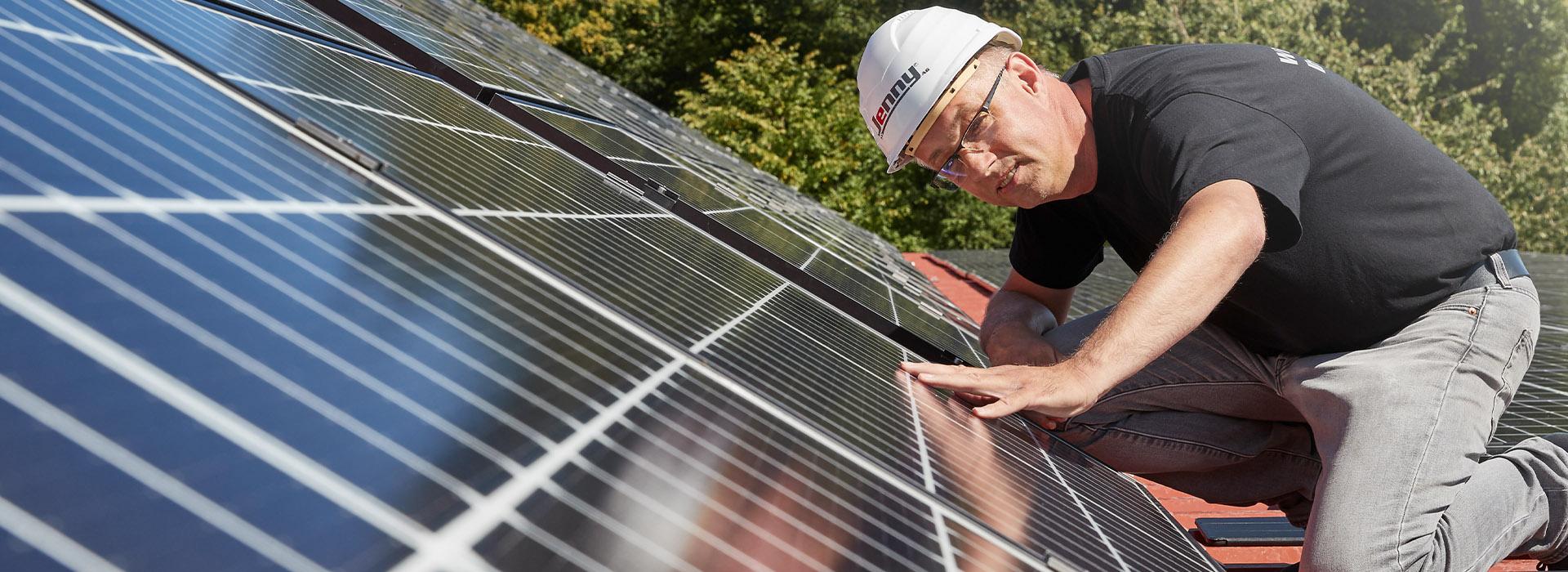 Energielösungen: eine Fachkraft der Solartechnik prüft die Installation der Solarplatten