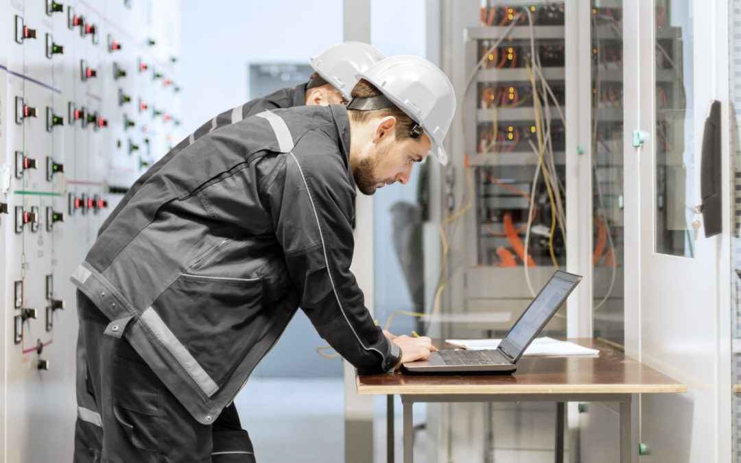 Energielösungen: zwei Elektroniker arbeiten an einem Laptop.