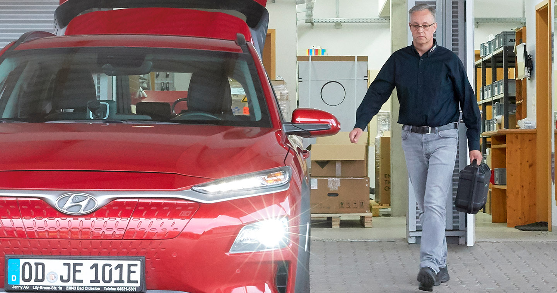 Energielösungen: ein modernes Elektroauto wird aufgeschlossen und wirft Licht (E-Mobilität)