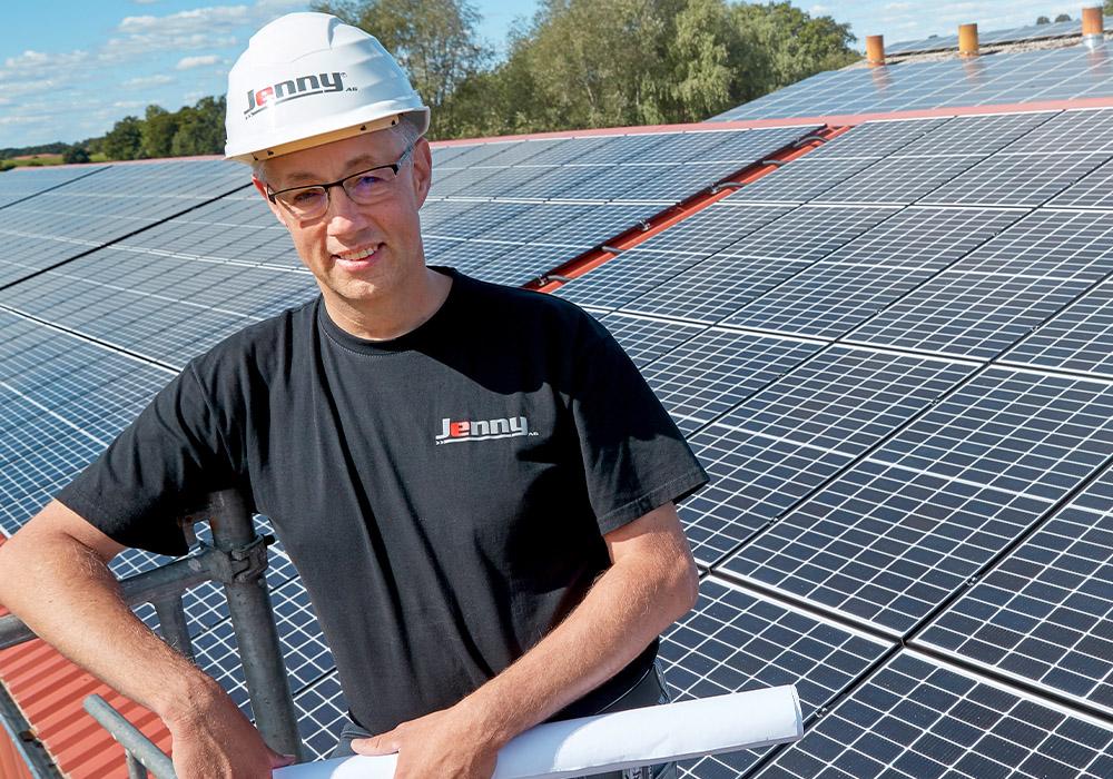 Energielösungen: eine Fachkraft für Elektrotechnik arbeitet auf einem Dach mit Solarplatten.