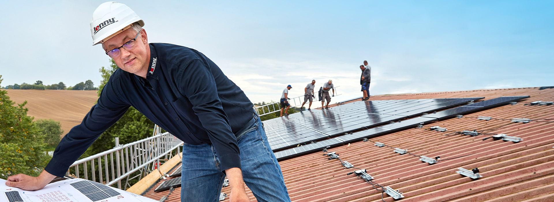 Energielösungen: Fachkräfte der Elektrotechnik arbeiten auf einem Dach und verlegen Solarplatten.