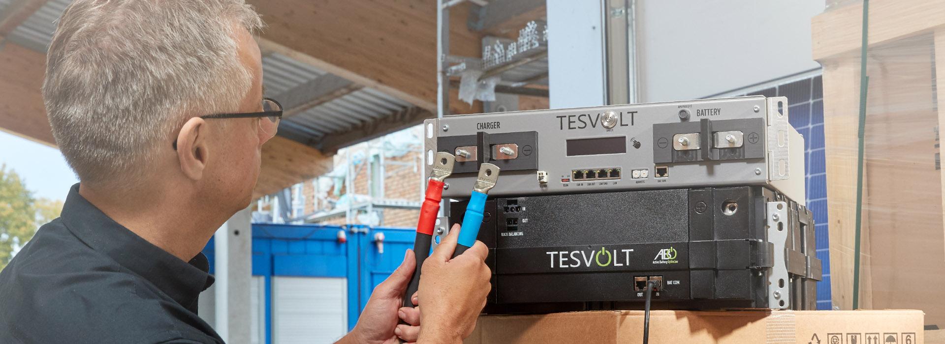Energielösungen: eine Fachkraft der Elektrotechnik misst Strom an einem Stromspeicher