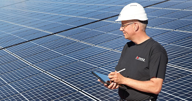 Energielösungen: ein Mitarbeiter der Elektrotechnik arbeitet auf einem Dach mit einer installierten Photovoltaikanlage