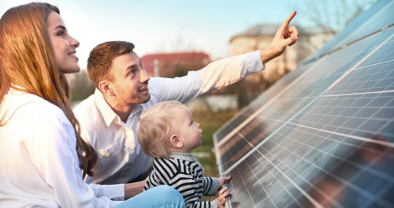 Energielösungen: eine junge Familie schaut sich Solarplatten aus der Nähe an