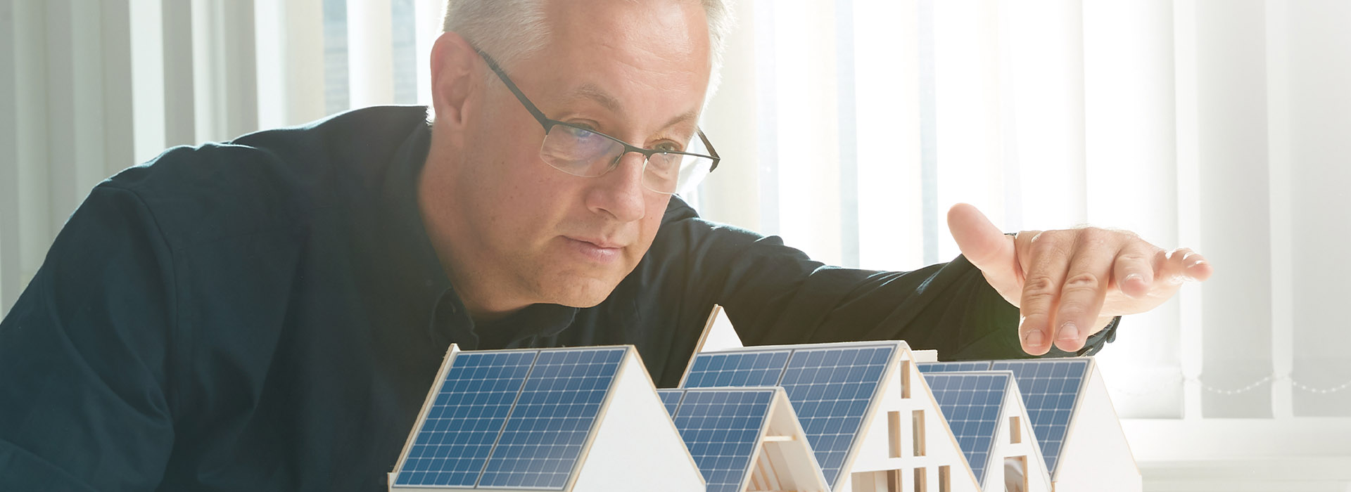 Energielösungen: ein Mitarbeiter visualisiert seine Ideen an einer Haus-Miniatur